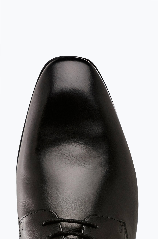 Kengät, joissa hillitty broguekuvio